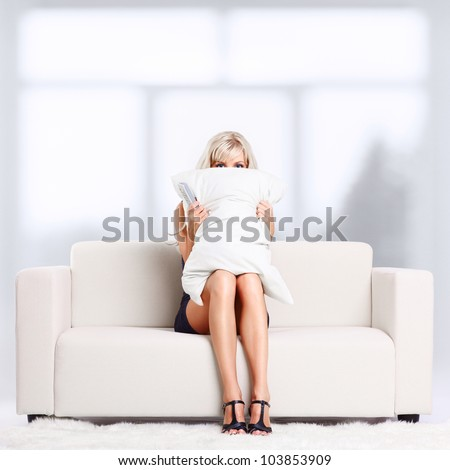 Young blond woman sitting on couch with remote control watching Halloween scary movie and hiding behind the pillow