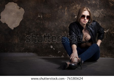 Young blond woman sitting on the floor of an dark old wall #76180624
