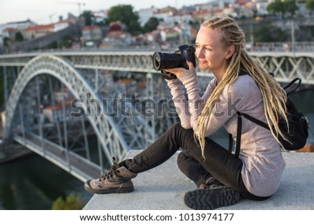 Young blond woman sitting with camera near Dom Luis I bridge across the Douro river in Porto, Portugal.
