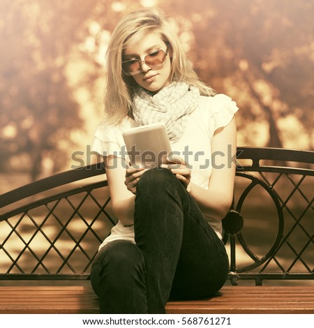 Young blond woman using tablet computer in city park  Stylish fashion model outdoor #568761271