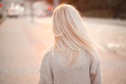 Young blond woman walks along the street