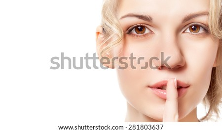 Young blond woman with a finger near her lips. Studio shot. Isolated on white background