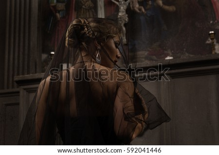 young blond woman with beautiful hairstyle is covered by a black veil in black dress kneeling at the altar in the background of paintings and arches and prays to Jesus