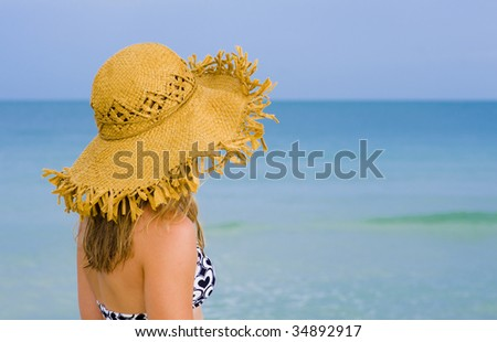 young blond woman with hat watching the sea