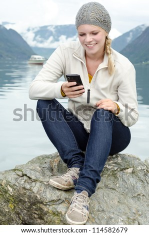 young blond woman with her Smartphone in the hand and a fjord in Norway in the background - stock photo