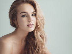 Young blond woman with long curly hair. Beautiful face of gorgeous girl with blue eyes. Nice portrait of a caucasian female looking at camera. Attractive fashion model