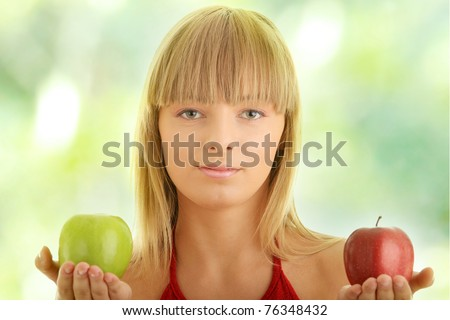 Young blond woman with red and green apples on her hand - making decision concept