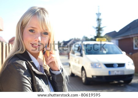young blond woman with smartphone in front of a and taxicab/young blond woman stands with a cell phone on a village street
