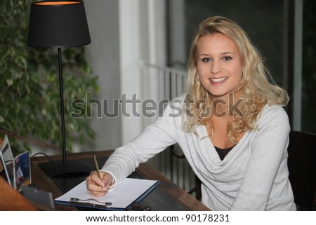 Young blond woman writing on clipboard