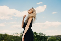 Young blonde attractive woman with long hair, wearing black maxi dress, outdoors, standing in a field in wind, on blue sky background.