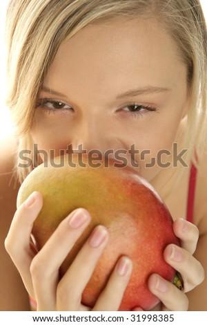Young blonde beauty woman eating mango