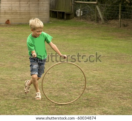 young blonde boy plays with a traditional wooden hoop and stick