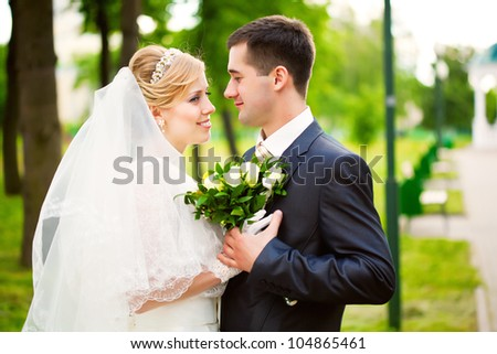 Young blonde bride and groom in walking the park