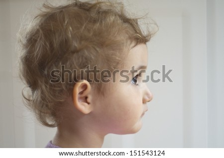Young blonde child, girl toddler, with blonde curly hair. Taken with plain backdrop, side on. She is looking into the distance. Beautiful. Head shot.