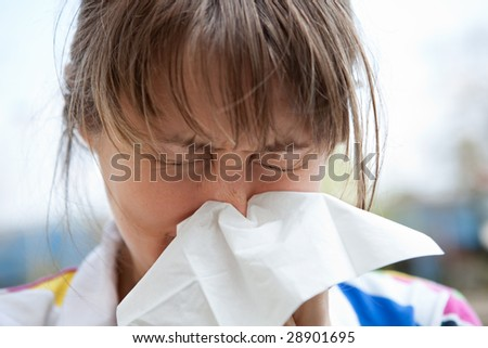 Young blonde female blowing her nose