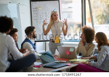 young blonde female caucasian explains business plan to other coworkers. business, passion, presentation,  Foto stock ©