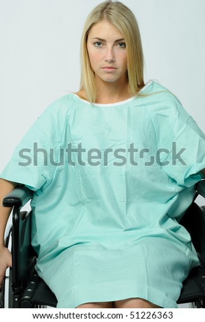 Young Blonde female patient sitting sadly in wheelchair wearing hospital gown