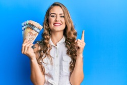 Young blonde girl holding canadian dollars smiling with an idea or question pointing finger with happy face, number one