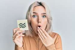 Young blonde girl holding paper with aquarius zodiac sign covering mouth with hand, shocked and afraid for mistake. surprised expression
