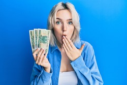 Young blonde girl holding 50 polish zloty banknotes covering mouth with hand, shocked and afraid for mistake. surprised expression