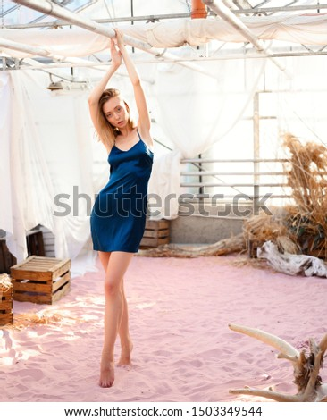 Young blonde girl in a blue nightgown. Fashion shot in the studio. #1503349544