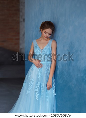 Young blonde girl in a luxurious blue dress with tulle and lace. Delicate natural make-up. Beautiful, elegant, high hairstyle for an average length of hair, with weaving. Evening image