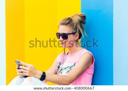 young blonde girl in sunglasses posing sitting on the floor near a colored wall, my phone and smart watch, girl in sneakers and jeans,works, photos,social networks,facebook, instagram,outdoor portrait #408000667