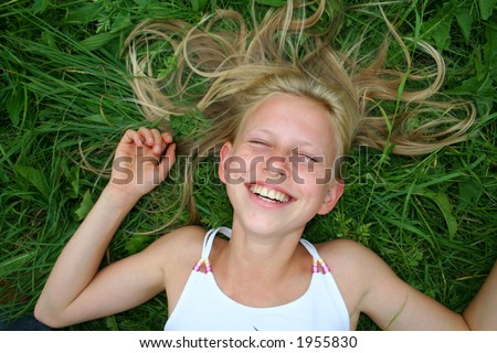 young blonde girl laughing in grass