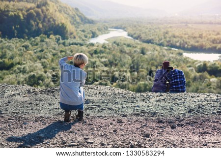 Young blonde girl photographer makes a photoshoot of hipster man and girl sitting together on the top of mountain at sunset backdrop. Traveling, tourism and friendships concept.