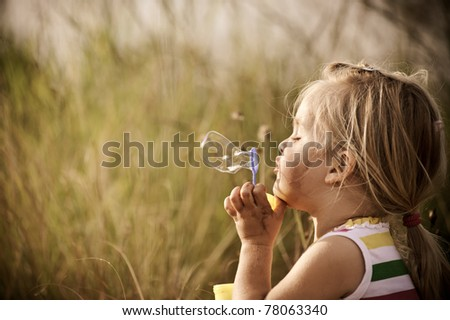 Young blonde girl plays in a field, blowing many bubbles