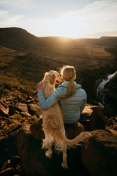 Young blonde girl sitting on mountain rock while dog looks at her overlooking river at sunset.
