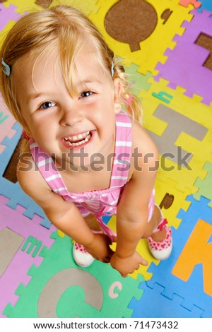 young blonde girl smiles as she learns the alphabet at playschool
