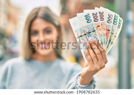 Young blonde girl smiling happy holding czech koruna banknotes at the city. Stock photo ©