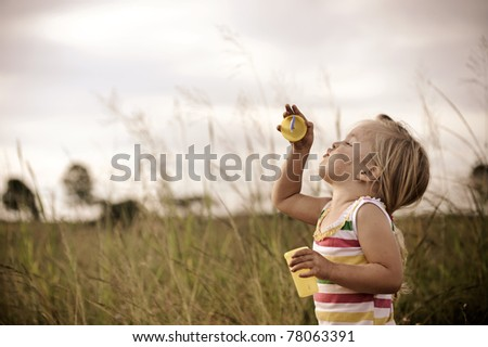 Young blonde girl trying to blow bubbles in a field graded with a vintage tone