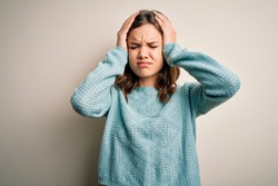Young blonde girl wearing casual blue winter sweater over isolated background suffering from headache desperate and stressed because pain and migraine. Hands on head.
