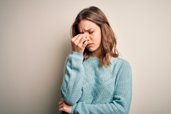 Young blonde girl wearing casual blue winter sweater over isolated background tired rubbing nose and eyes feeling fatigue and headache. Stress and frustration concept.