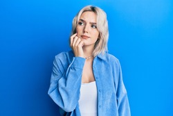 Young blonde girl wearing casual clothes thinking concentrated about doubt with finger on chin and looking up wondering