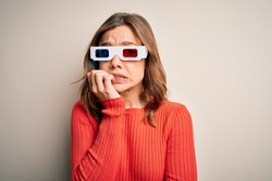 Young blonde girl wearing 3d cinema glasses over isolated background looking stressed and nervous with hands on mouth biting nails. Anxiety problem.