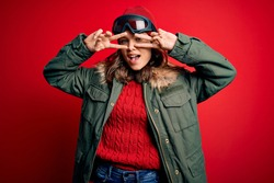 Young blonde girl wearing ski glasses and winter coat for ski weather over red background Doing peace symbol with fingers over face, smiling cheerful showing victory