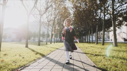 Young blonde girl with a pink backpack in school uniform is walking quickly in the park on path at sunny autumn weather, looking around and smiling. Trees along the way, front view.