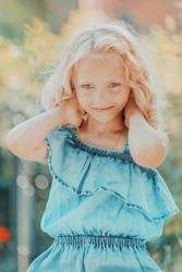 young blonde girl with curly hair straightens her hair. High quality photo