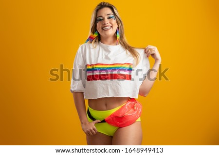 Young blonde hair woman in costume enjoying the carnival party covering with lgbt pride t-shirt. Alone. One. LGBT flag. LGBT+ symbol on yellow background.