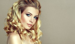 Young, blonde  haired woman with voluminous hair.Beautiful model with long, dense, curly hairstyle .