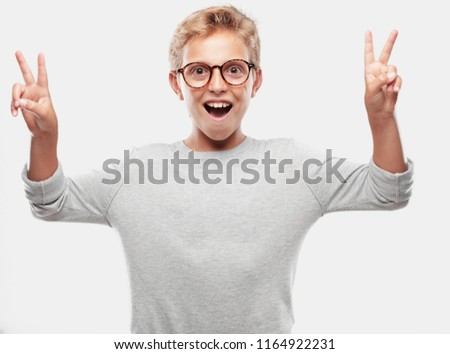 young blonde handsome boy with a proud, happy and confident expression; smiling and showing off success while gesturing victory with both hands, giving an