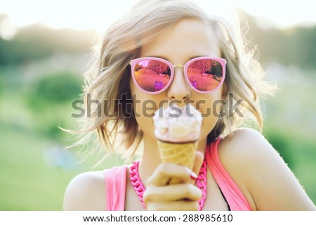 Young blonde hipster girl eating a delicious ice cream in summer hot weather in sunglasses have fun and good mood looking in camera and smiling.