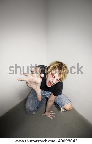 Young blonde male zombie reaching towards the camera - stock photo