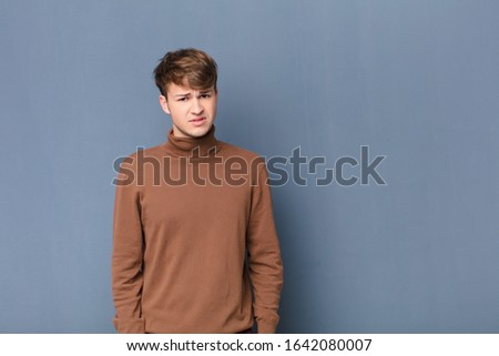 young blonde man feeling puzzled and confused, with a dumb, stunned expression looking at something unexpected isolated against flat wall