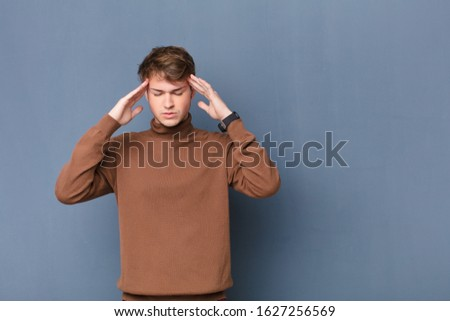 young blonde man looking concentrated, thoughtful and inspired, brainstorming and imagining with hands on forehead isolated against flat wall