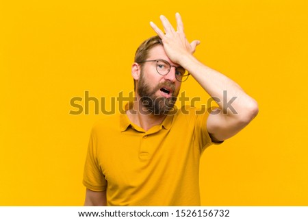 young blonde man raising palm to forehead thinking oops, after making a stupid mistake or remembering, feeling dumb against orange wall