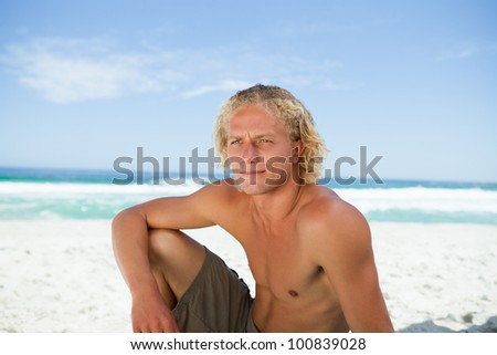 Young blonde man sitting on the beach while attentively looking towards the side